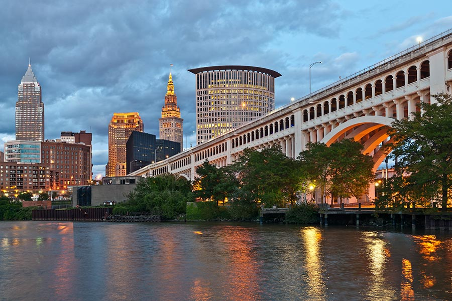 Blog - Cleveland Skyline Lighting up for the Evening, a Bridge on the Right, Lights Reflecting off the Water