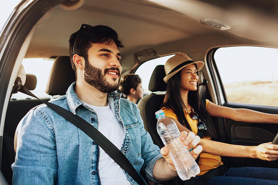 Personal Insurance - Young Parents and Son Take a Drive in Their Car, Smiling, Dad Having a Bottle of Water