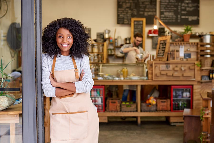 Specialized Business Insurance - Woman Stands Outside Her Shop, Wearing an Apron and Looking Proud